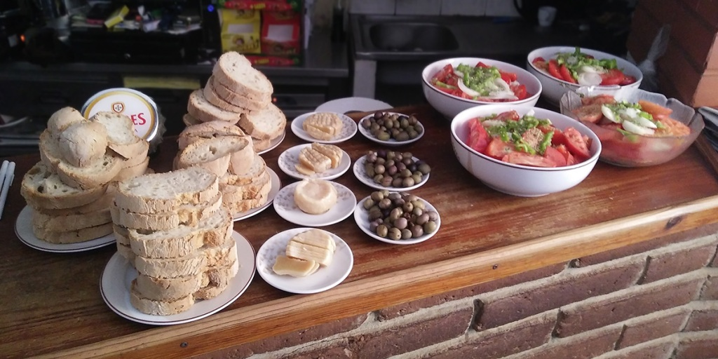 Selection of breads, cheeses, olives and tomato salads, all laid out in white crockery on a wooden counter top