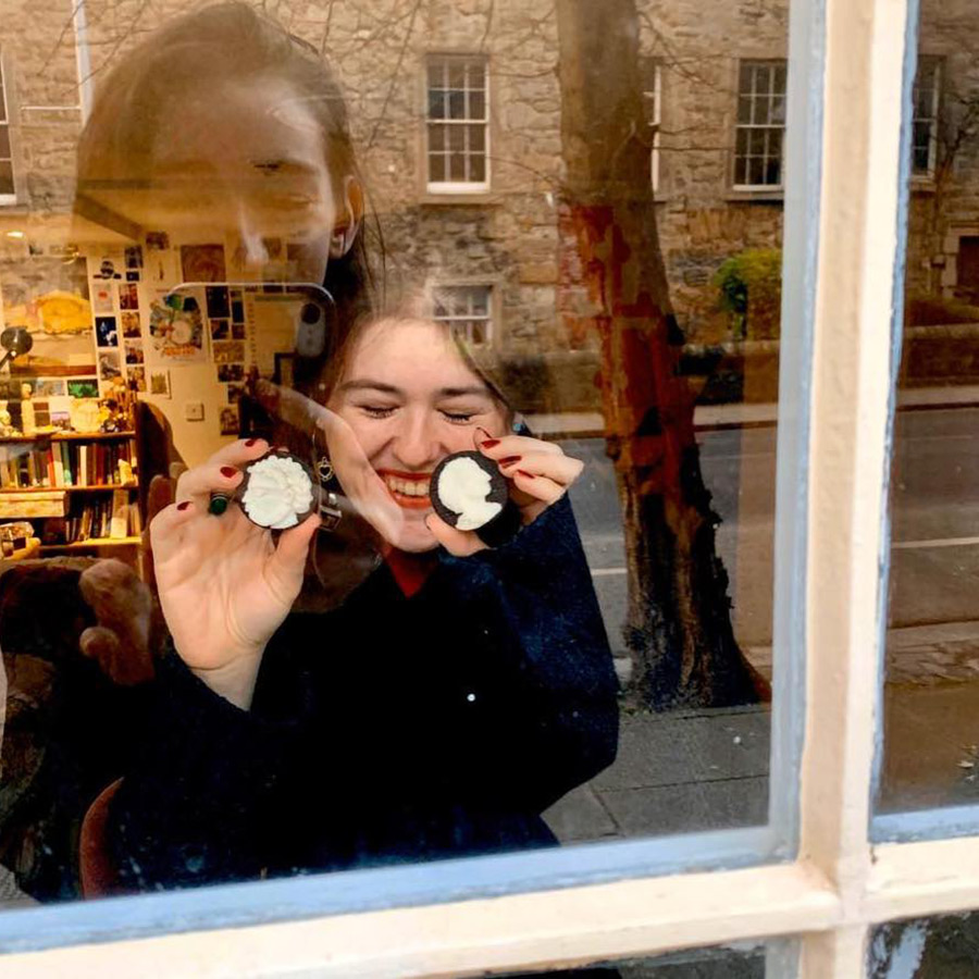 Carolyn holding up two carved oreos to a window, for a visitor to see