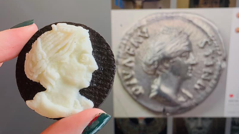 comparing carved oreo cookie to picture of original coin