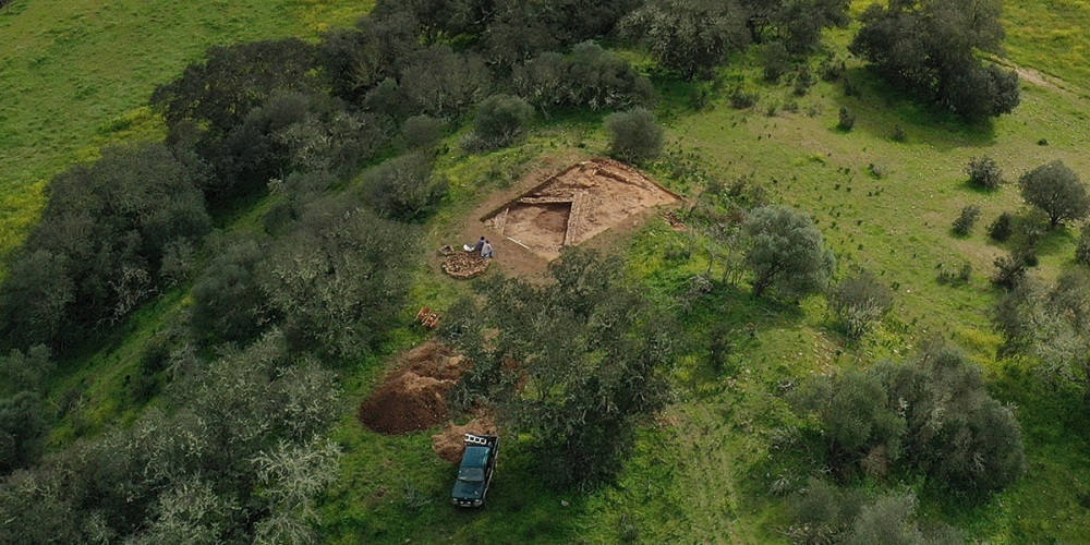 Aerial view of archaeological dig site among trees. Two people sitting viewing exposed remains of a building